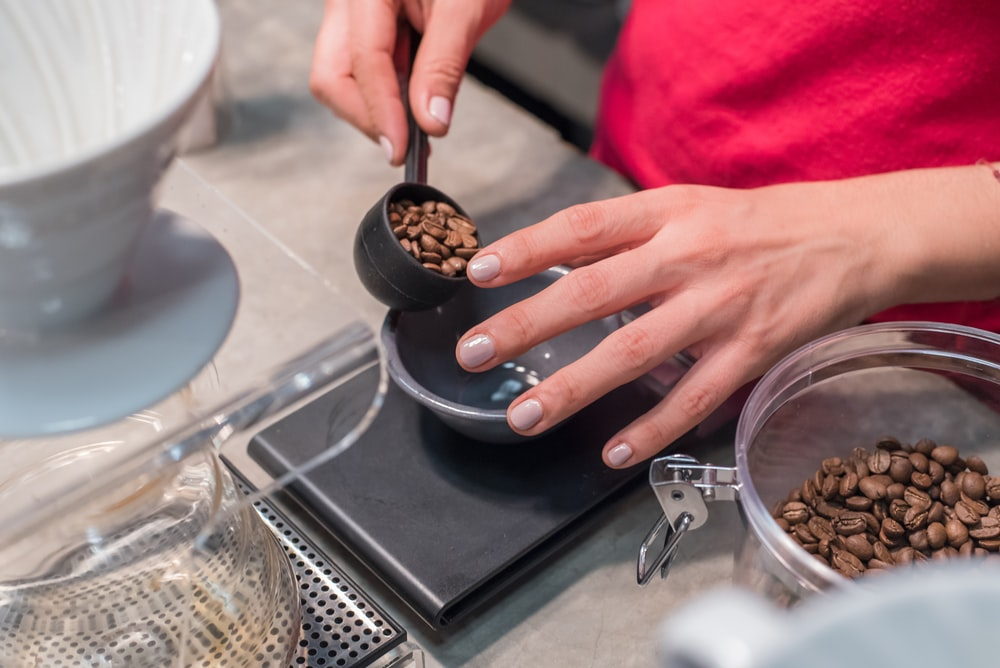 person scooping and measuring coffee beans