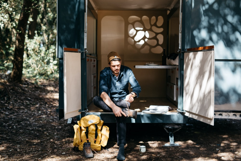 man sitting in the trailer while tieing his shoes