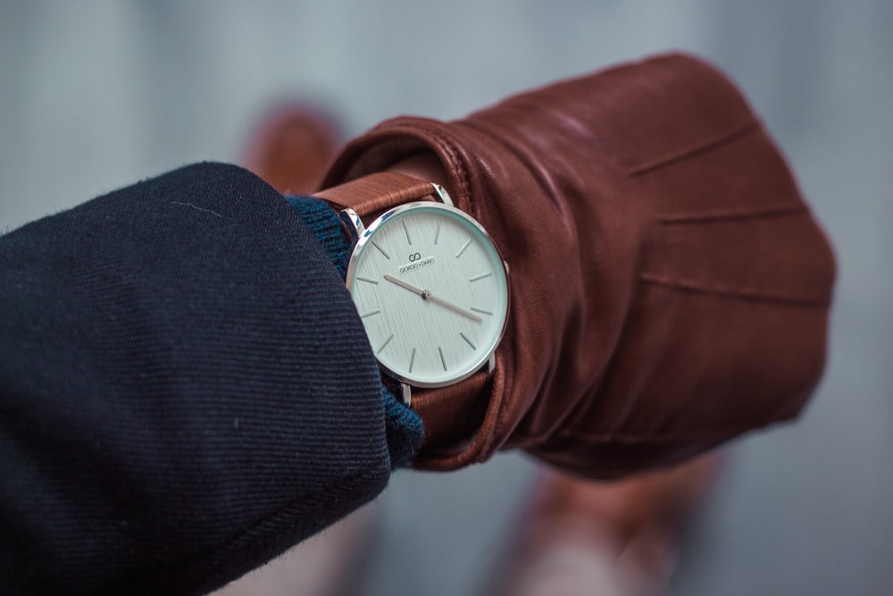 person looking at round white analog watch at 10:22