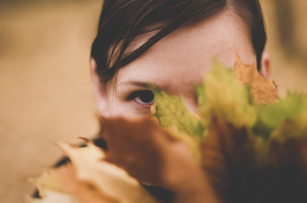 selective focus photo of woman hiding on green and brown leafed plant