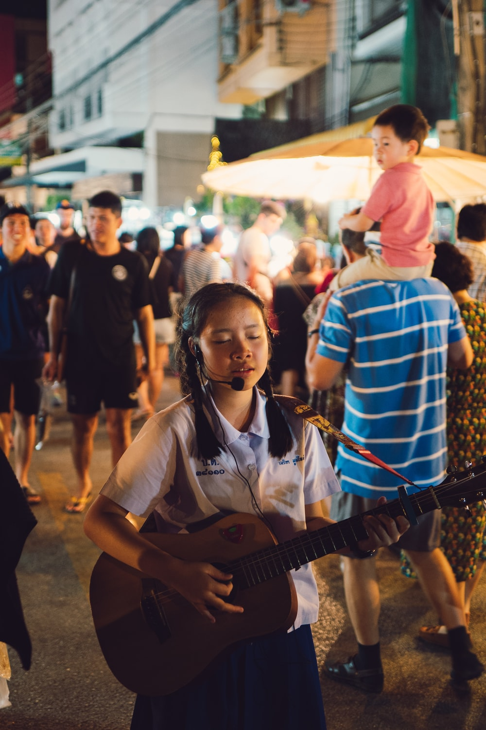 selective focus photo of girl playing guitar and singing
