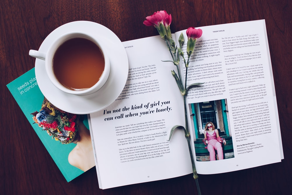 opened book with pink flower on top near filled ceramic mug