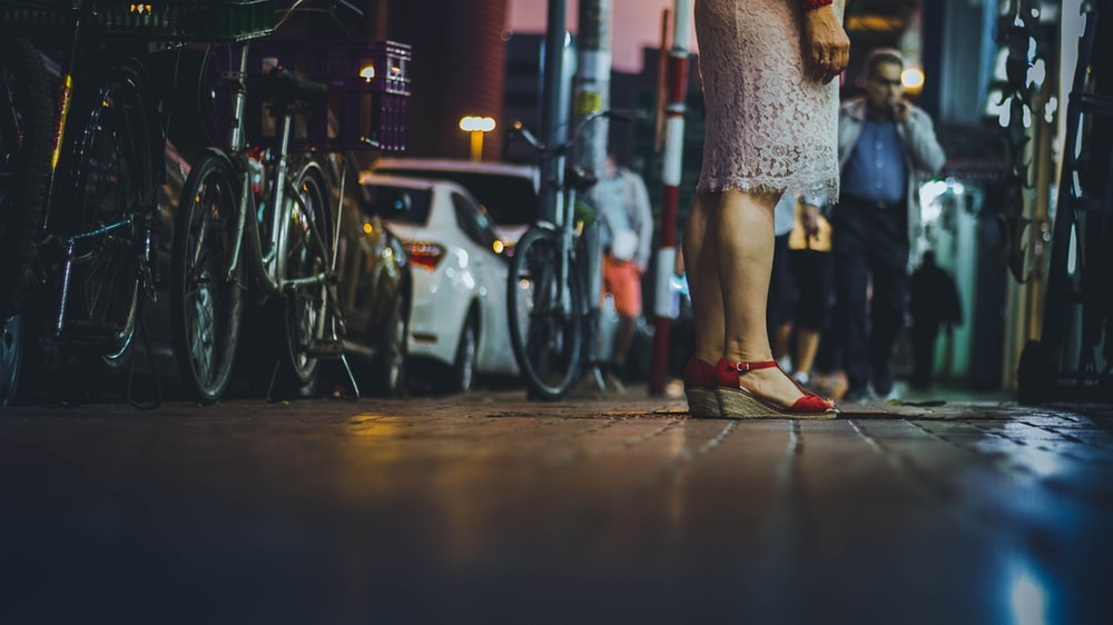 woman standing on street beside parked bikes