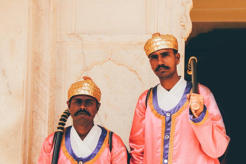 two men holding black wooden stick