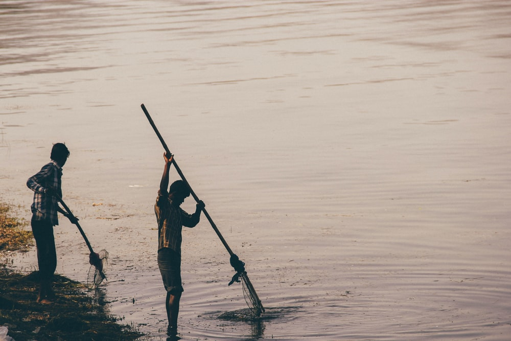 two men fishing on body of water at daytime