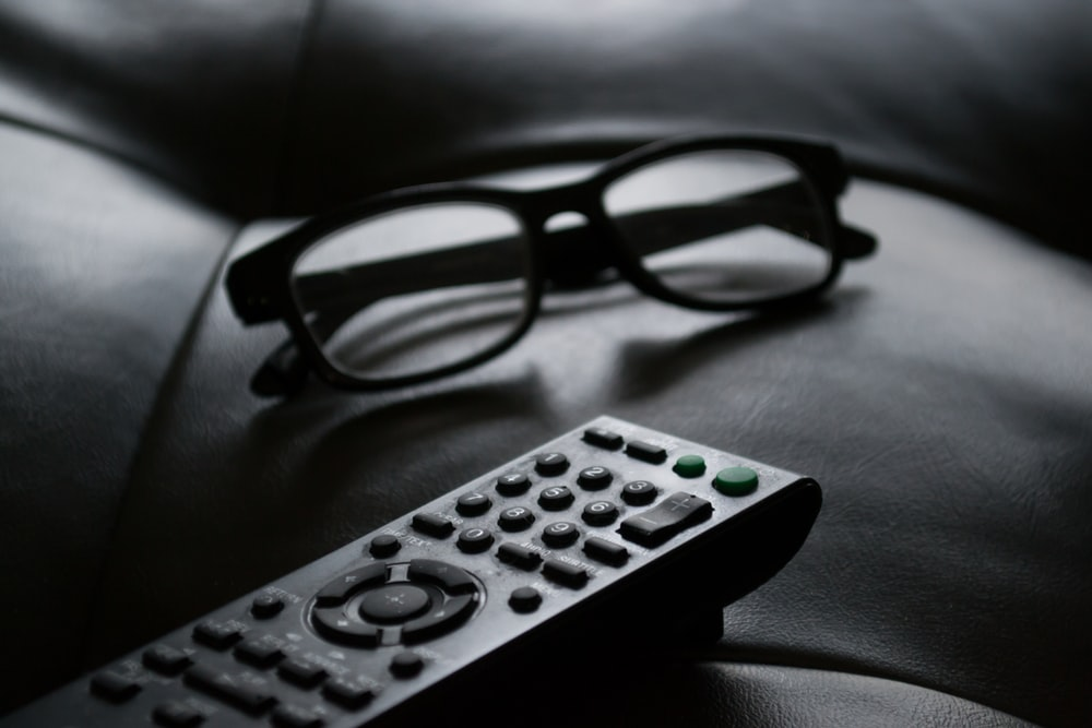 grayscale photo of remote beside eyeglasses