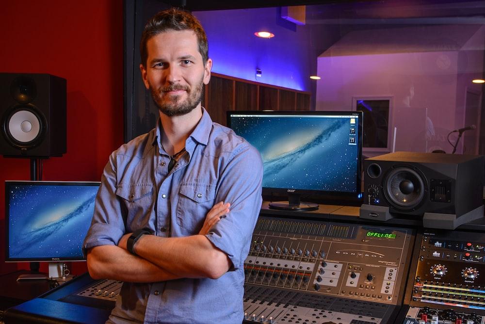 man standing behind audio mixer in studio