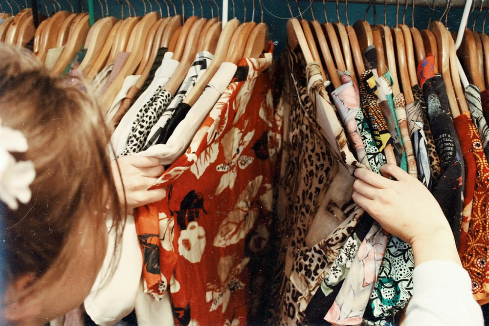 person holding assorted clothes in wooden hanger