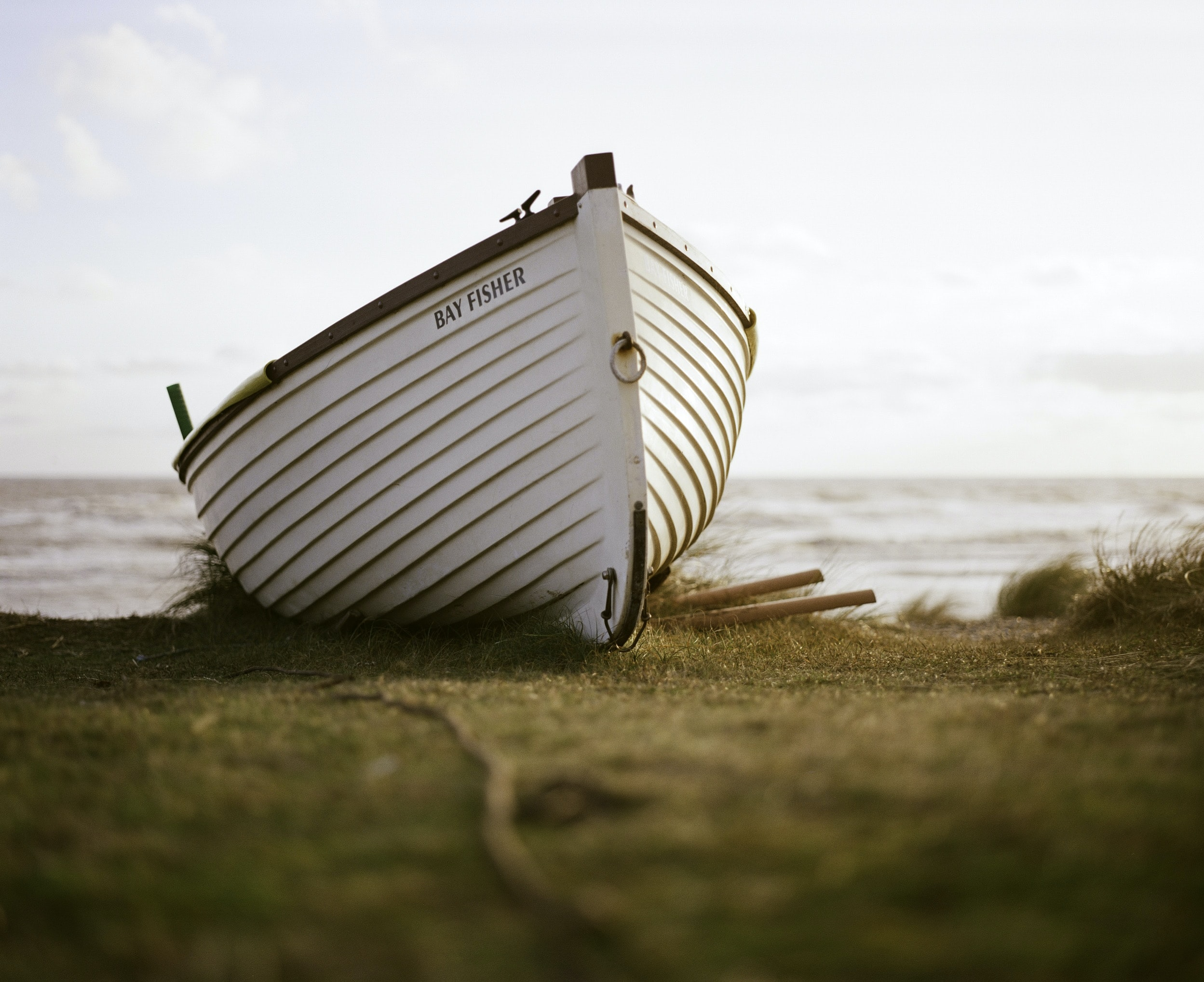 white boat on green grass field under gray sky