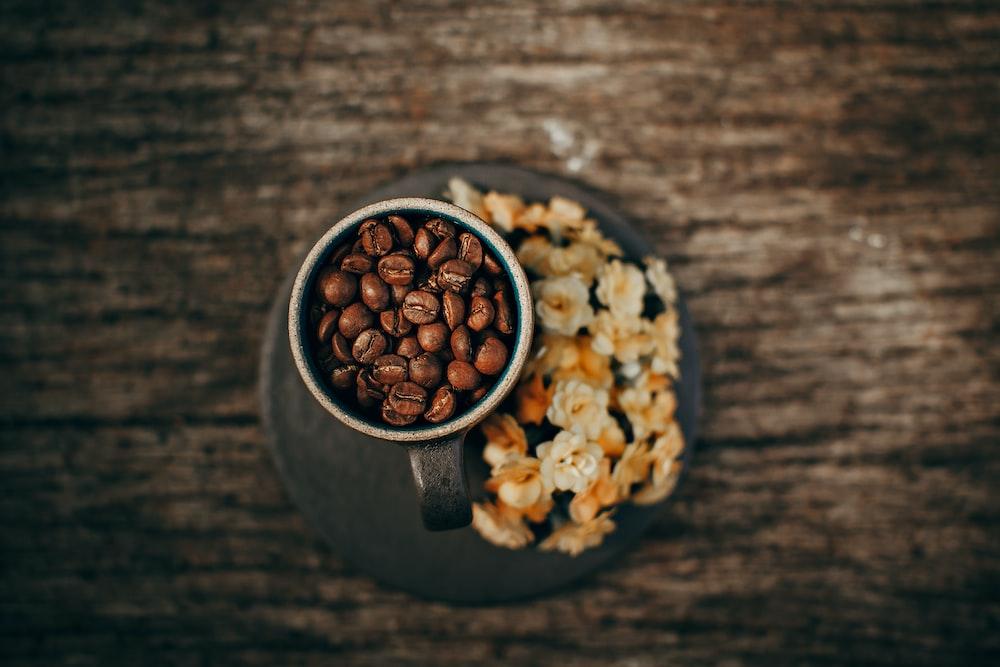 brown coffee beans on gray mug