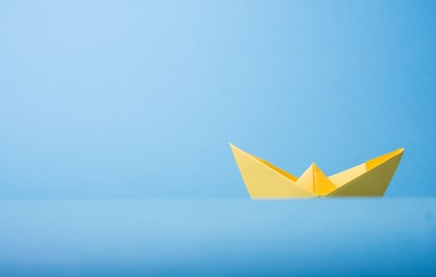closeup photo of yellow paper boat minimal teams background