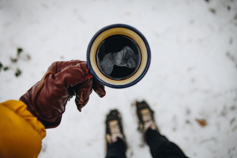 person holding coffee mug with black coffee