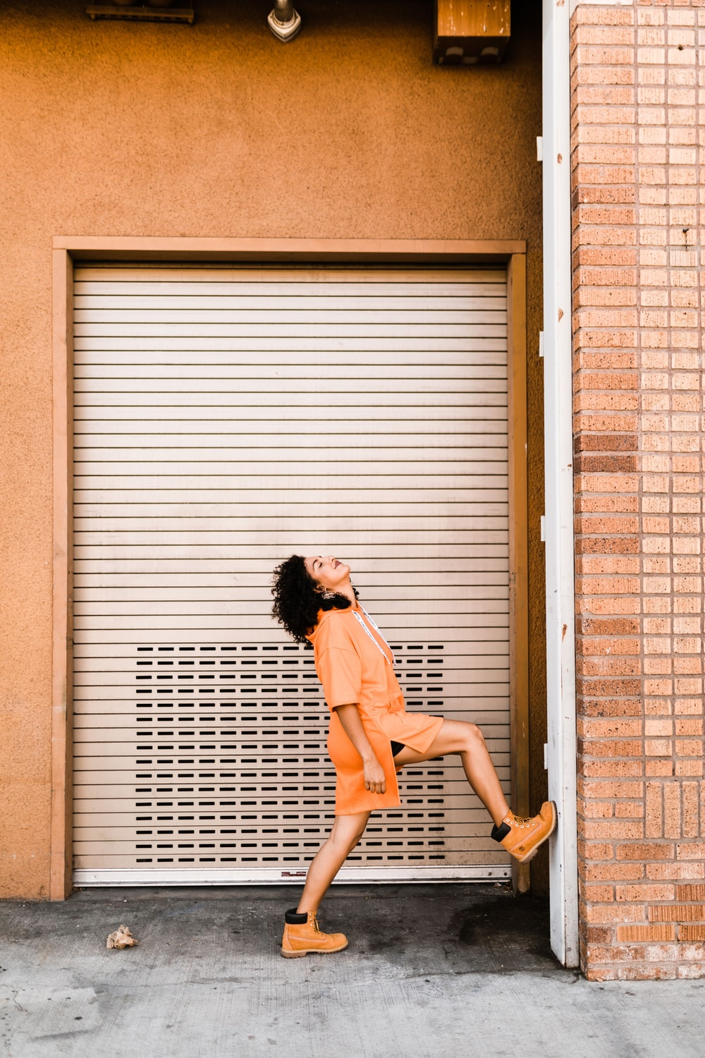 woman stepping her right foot on wall near roller shutter