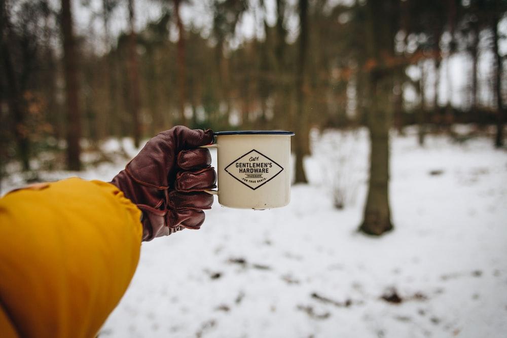 person holding camping mug