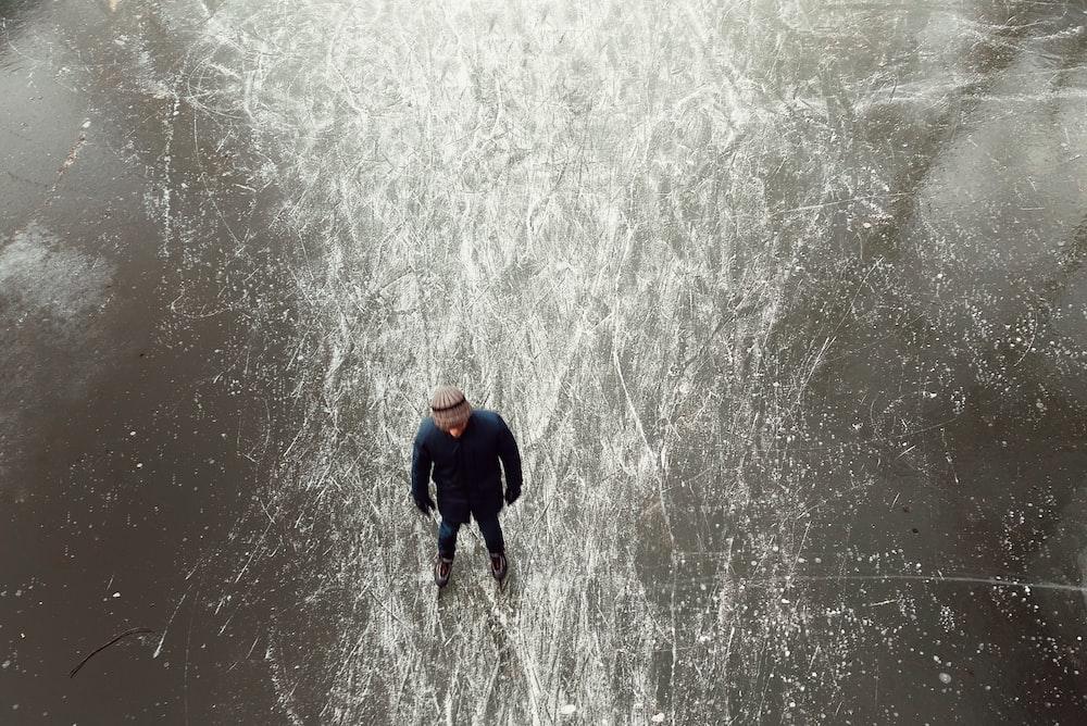 man wearing black jacket standing on frozen body of water during daytime