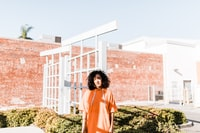 woman in orange pullover hoodie standing near white gate during daytime
