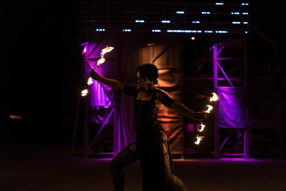 woman holding fire dancing rod while dancing on stage
