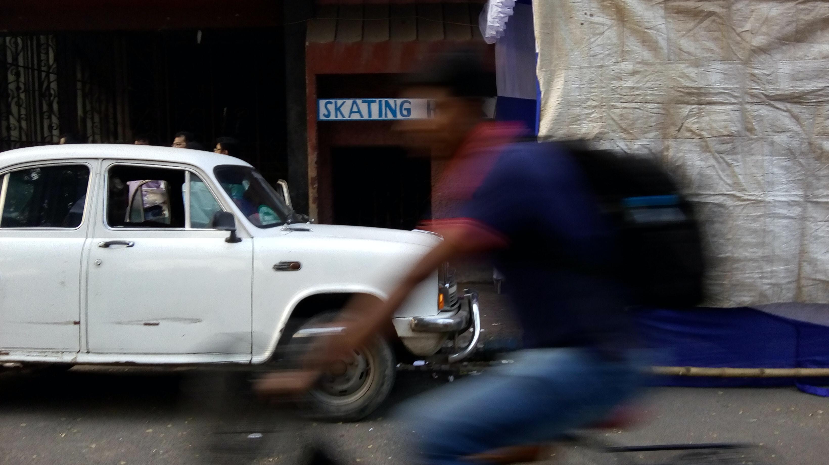 man riding bicycle beside white car
