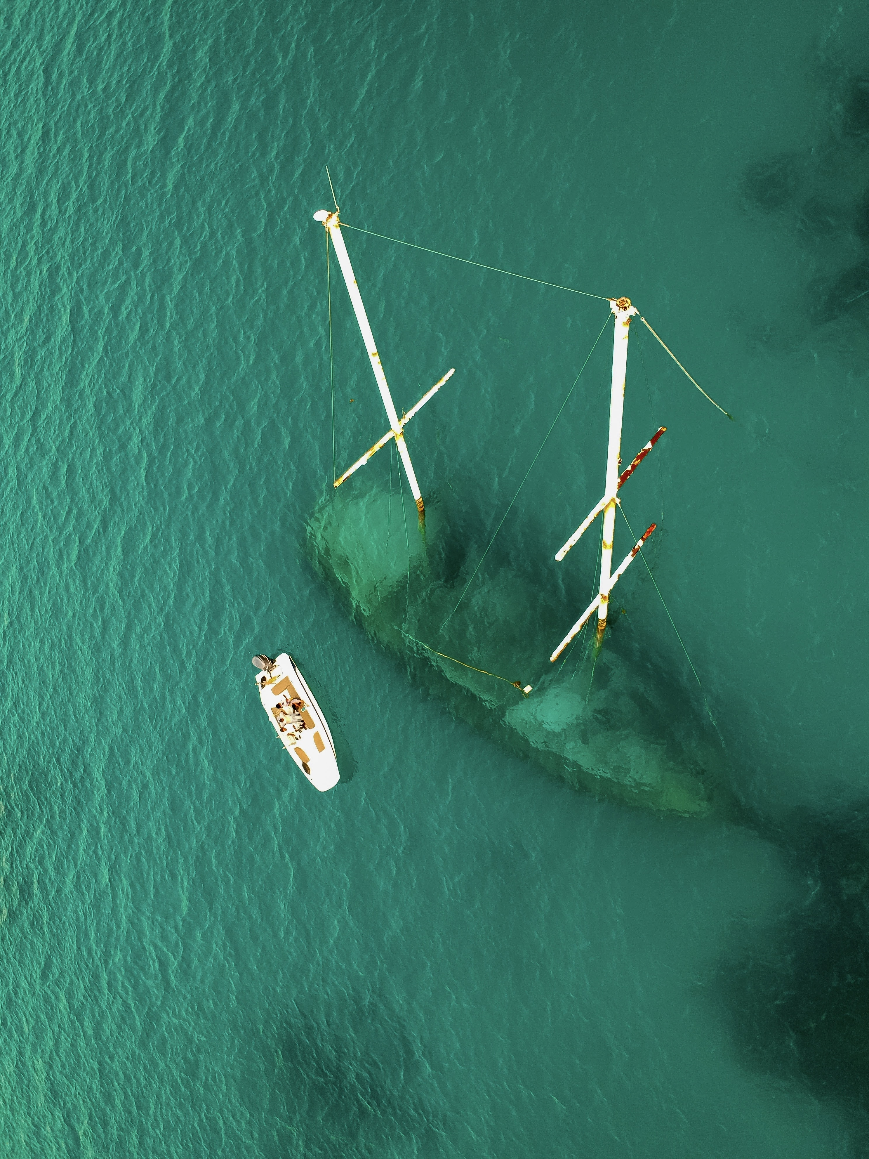 aerial view of green body of water with sank ship