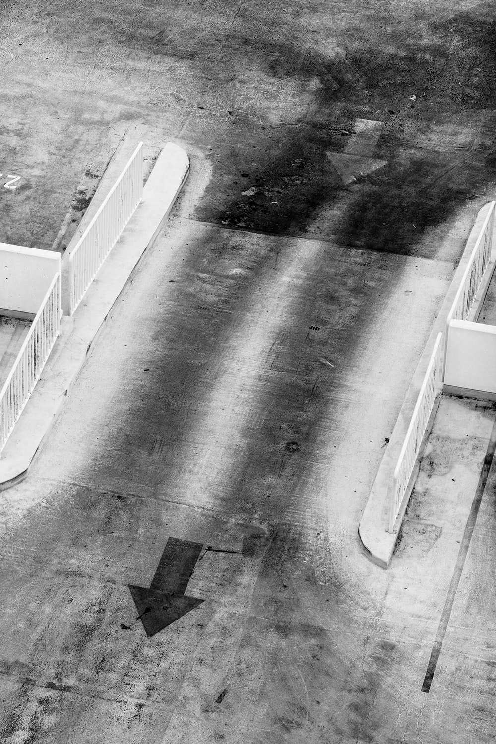 grayscale photography of concrete rod with arrows