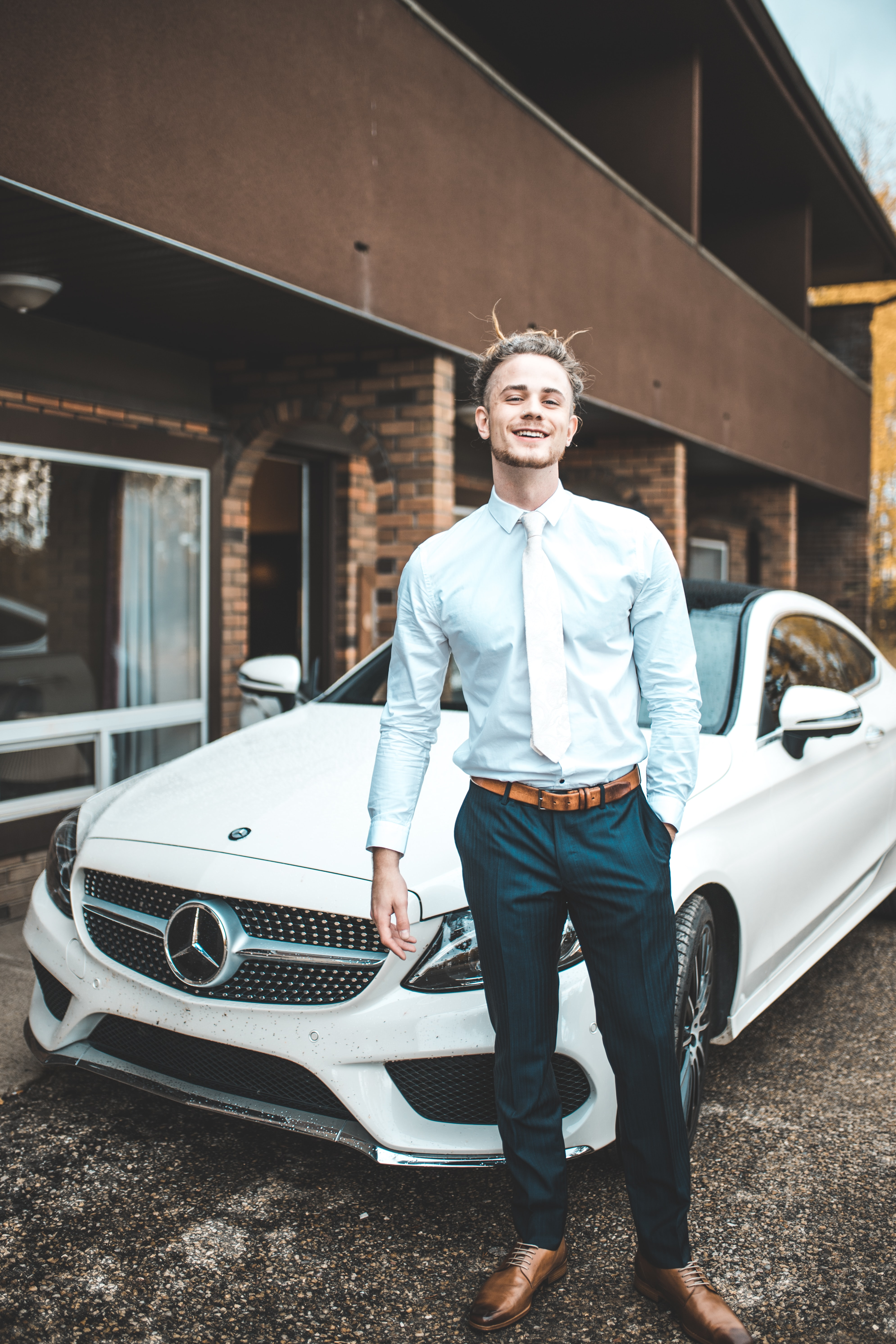 man standing in front on white Mercedes-Benz coupe