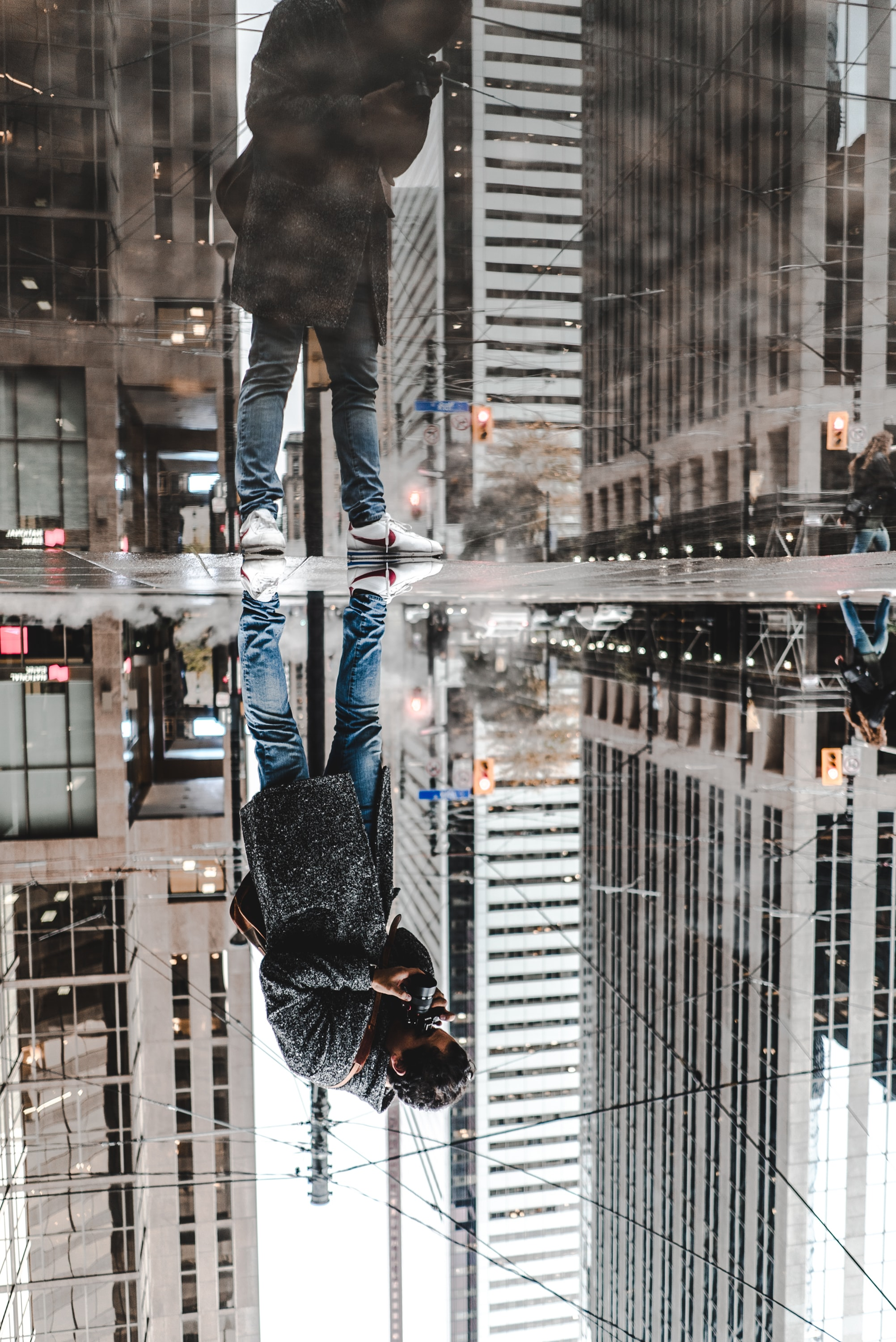 water mirror reflection photography of man standing on pavement front of buildings