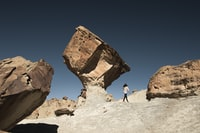 woman standing under brown rock formation at daytime