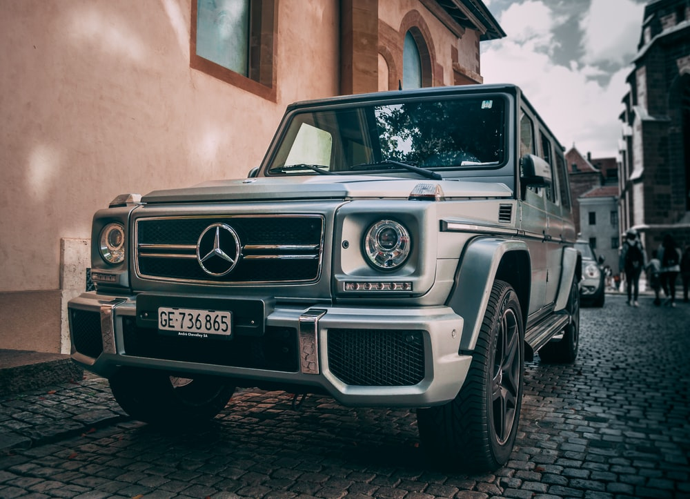 gray Mercedes-Benz vehicle beside house