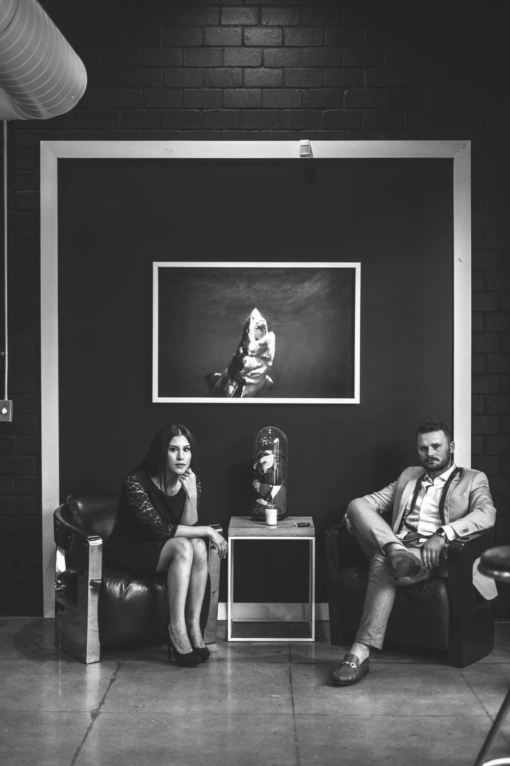 grayscale photo of man and woman sitting on sofa chairs