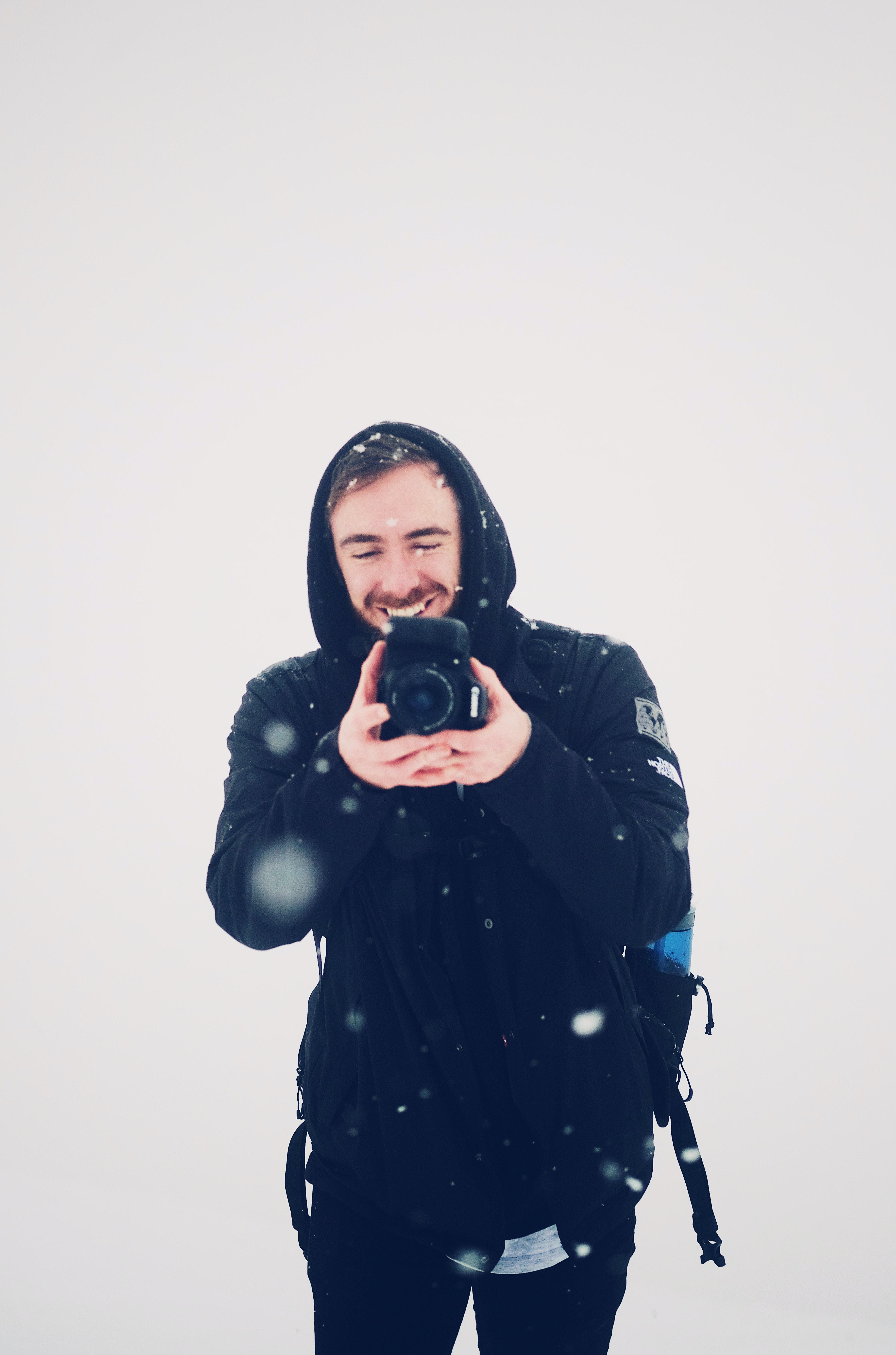 smiling man using DSLR camera