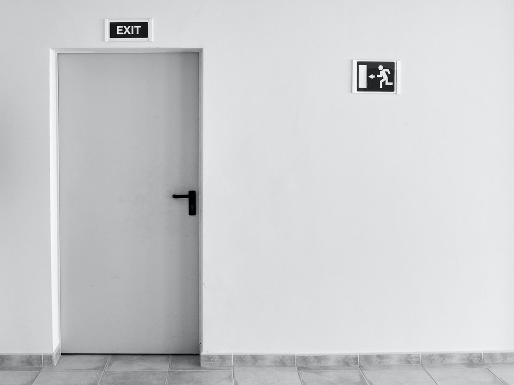 closed white painted door with exit signage