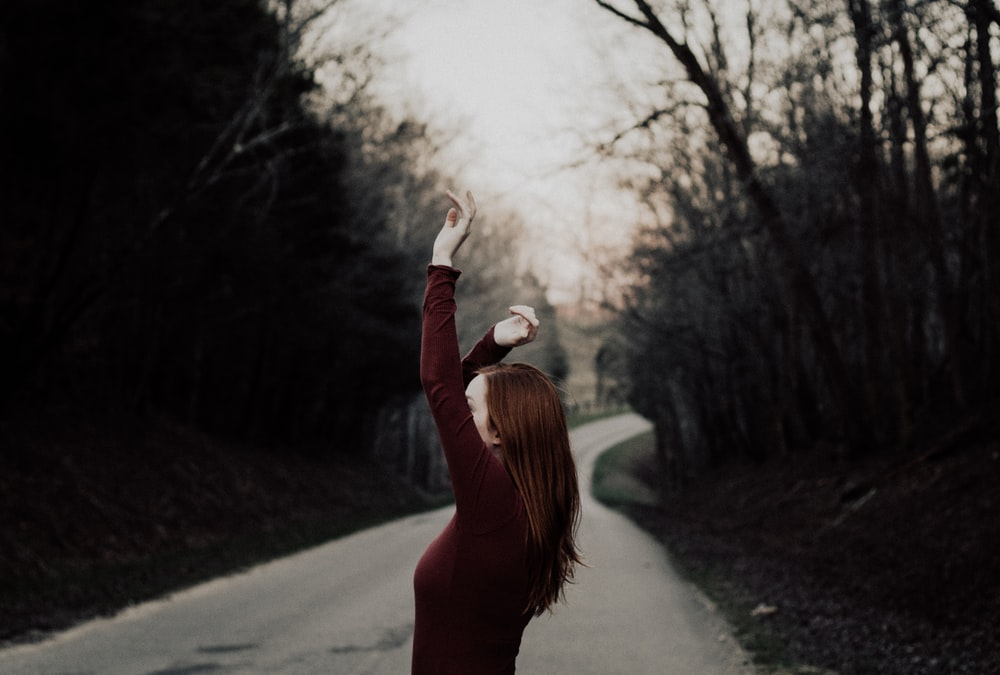 selective focus photography of female raising hands in the middle of the road surrounded by withered trees