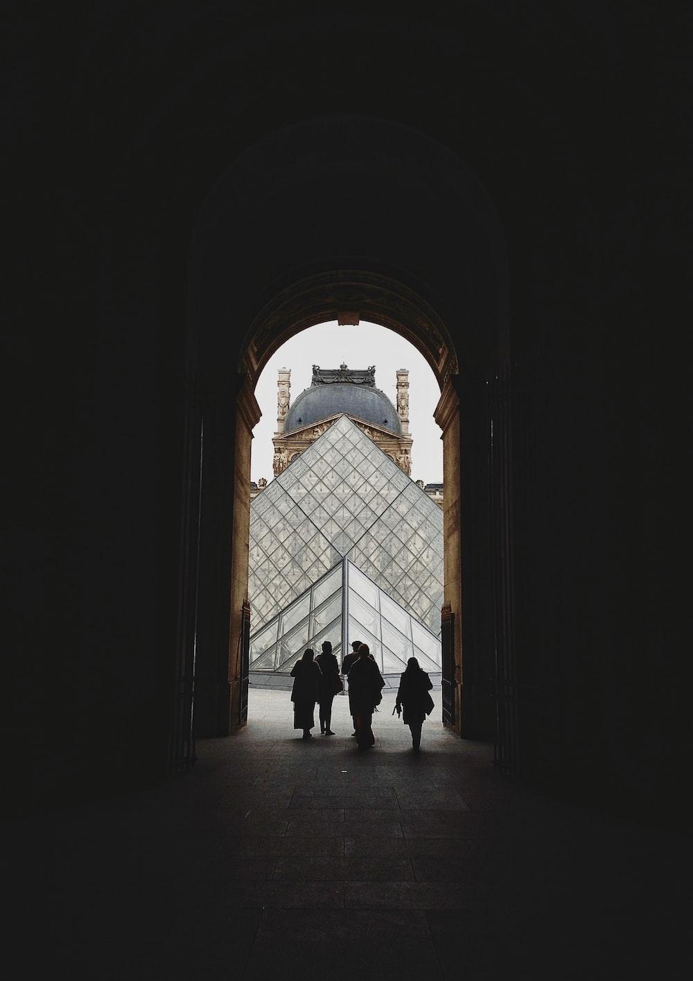 silhouette of people walking out of door