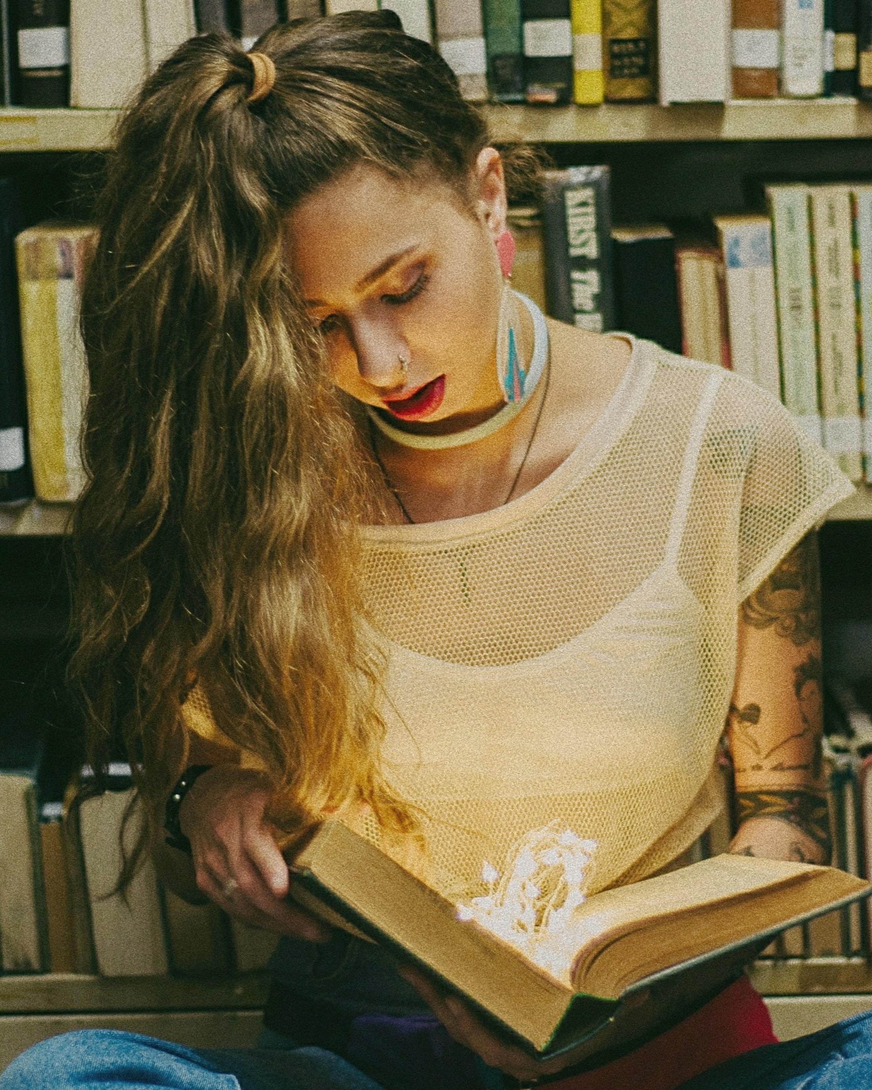 woman wearing white spaghetti strap dress reading book inside library