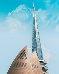 low angle photography of curtain-wall tower building under blue skies during daytime