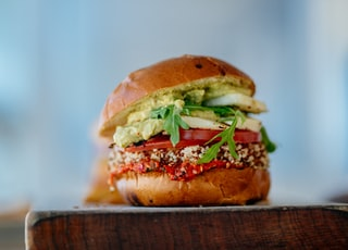 selective focus photography of hamburger with sliced tomatoes and vegetables