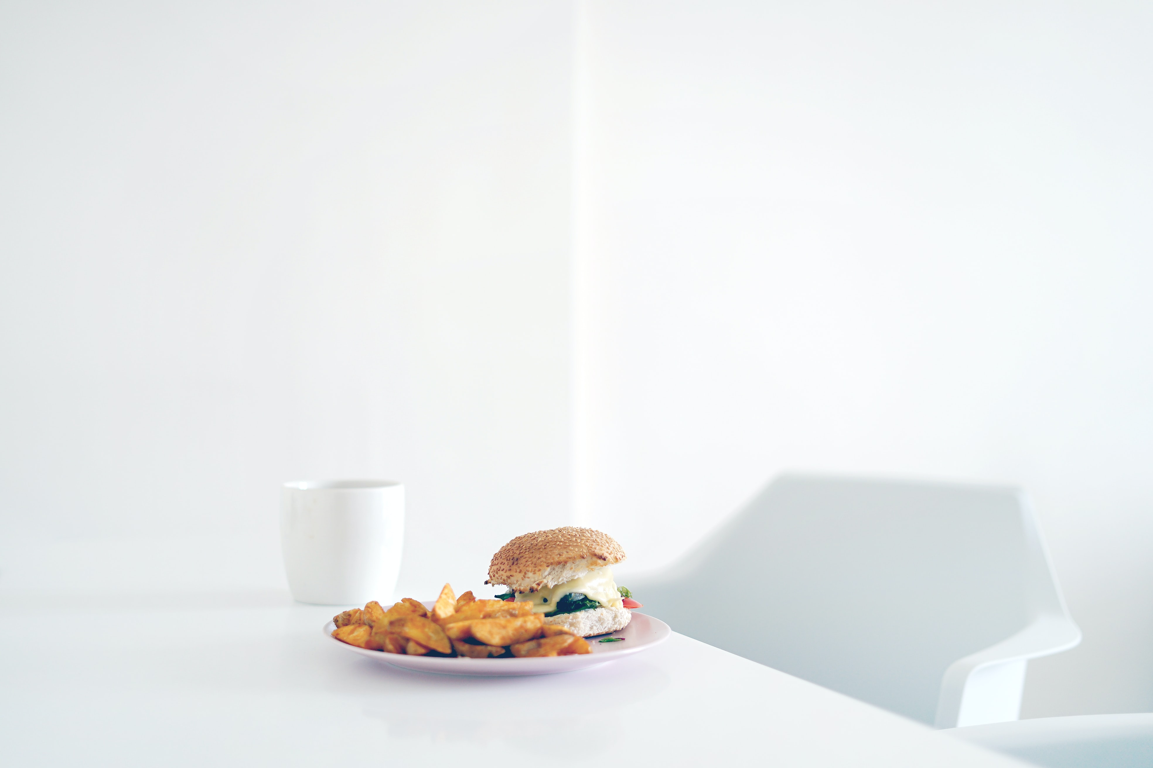 burger on plate beside mug