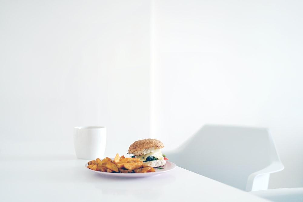 burger on plate beside mug