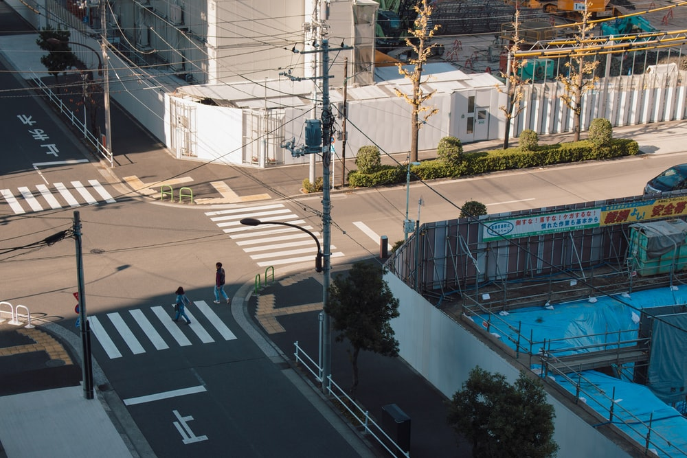 man and woman crossing pedestrian lane