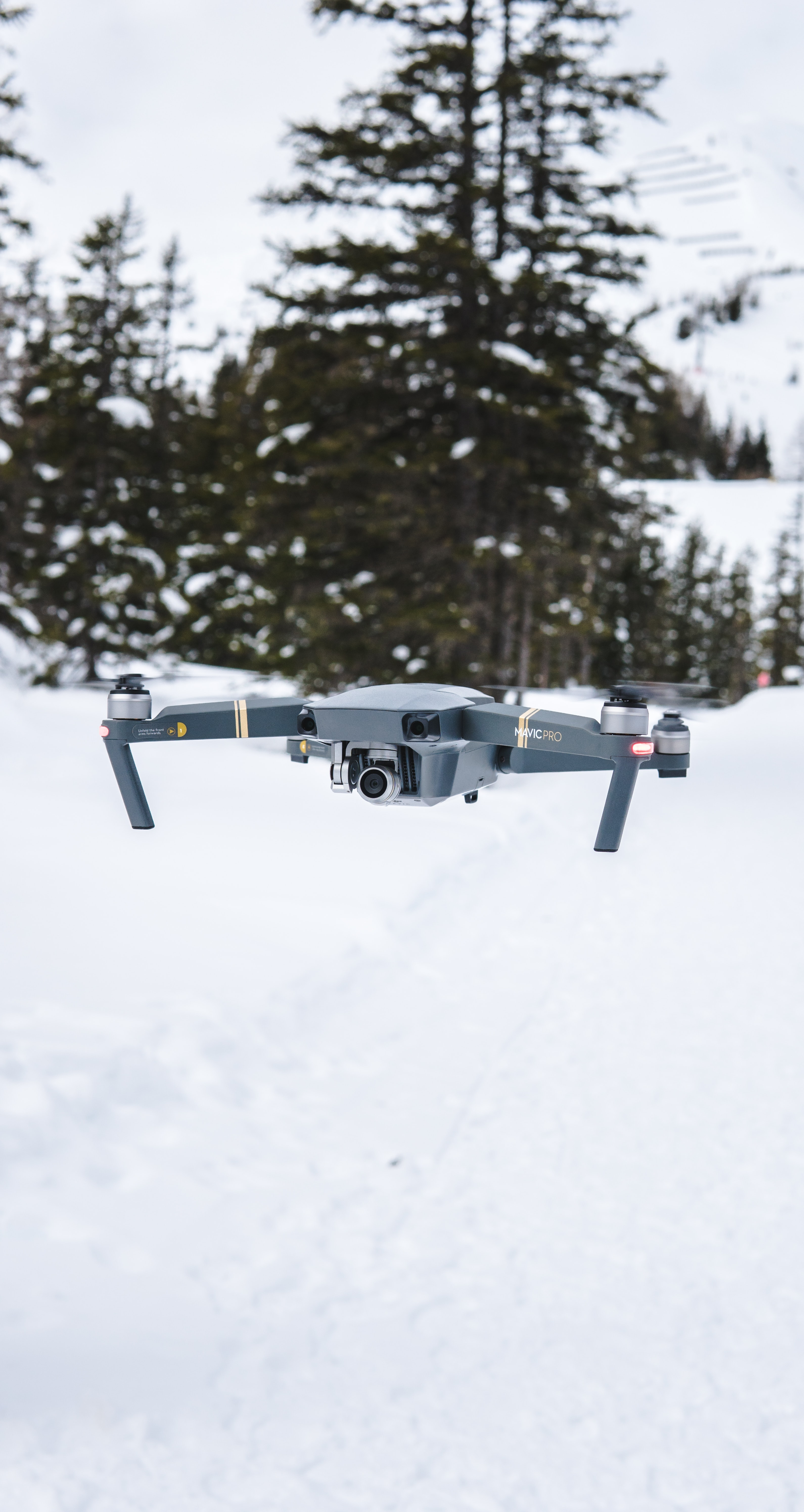 gray flying quadcopter near trees with snow