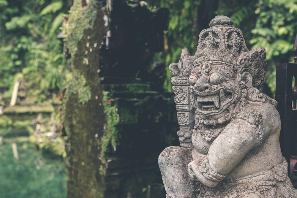 gray statuette near plants