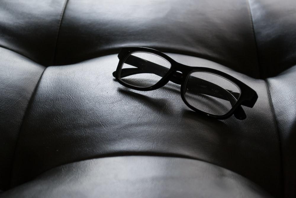 black framed eyeglasses on tufted leather
