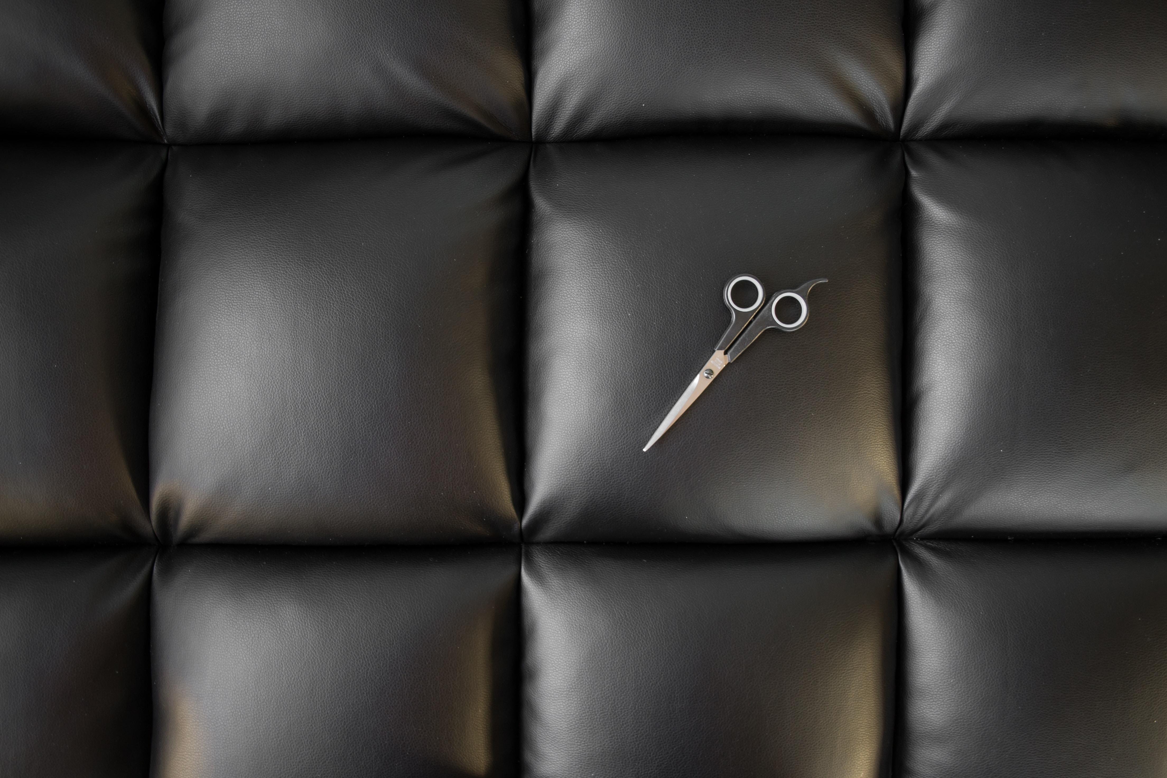 gray metal scissors on black leather pad