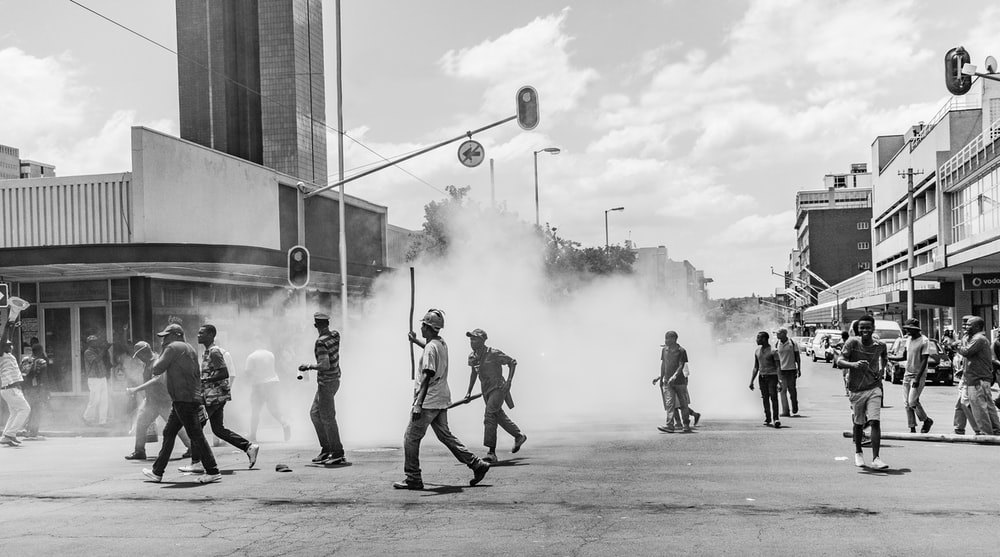 grayscale photo of people on street near buildings during daytime