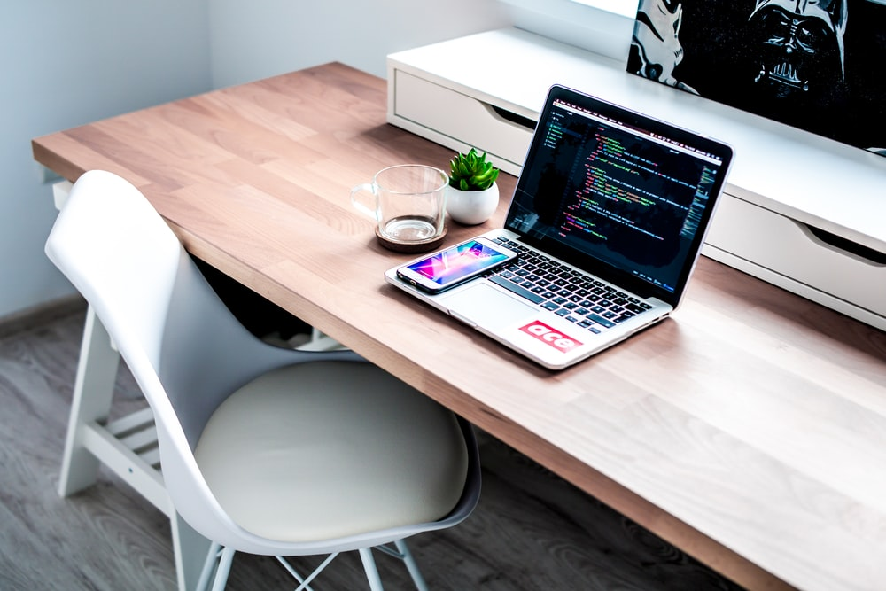 smartphone on laptop computer on top of brown wooden desk