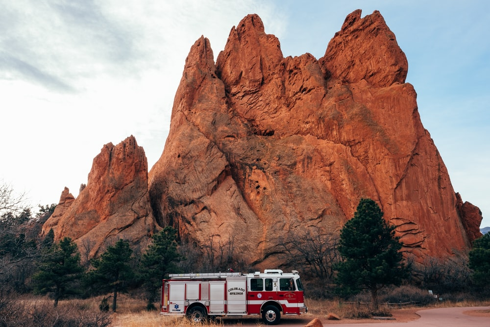 white and red firetruck near brown rock formation
