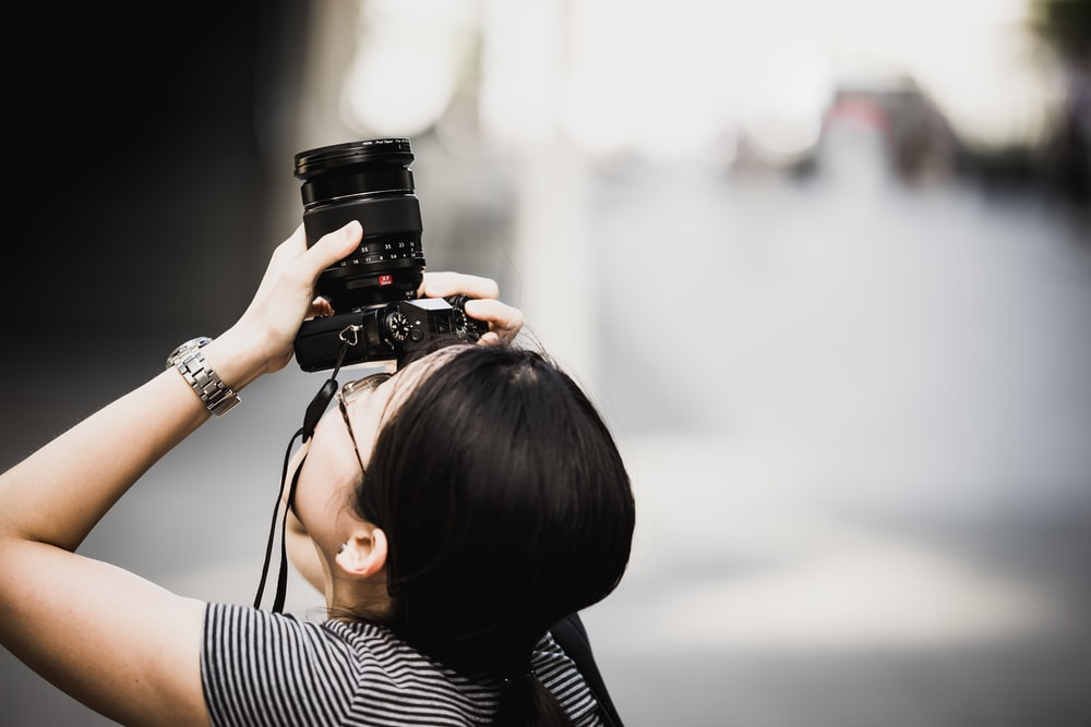 woman holding DSLR camera while focusing on top