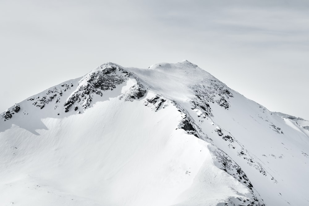 mountain covered with snow under white clouds
