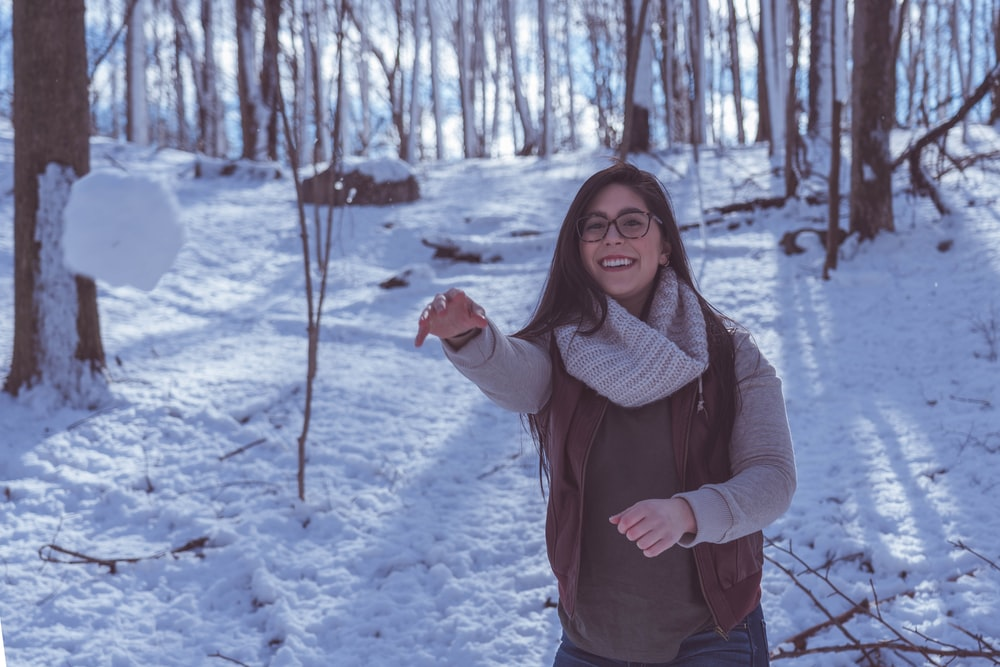 smiling woman wearing sweatshirt on snow covered ground