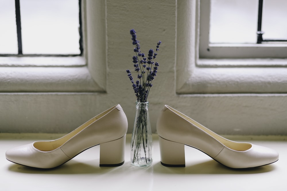 paid of beige shoes and lavender flowers